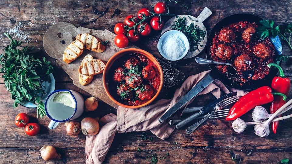 Spanische Tapas für zuhause: Lecker würzige Albondigas in köstlicher Tomatensoße – dazu passt Baguette.