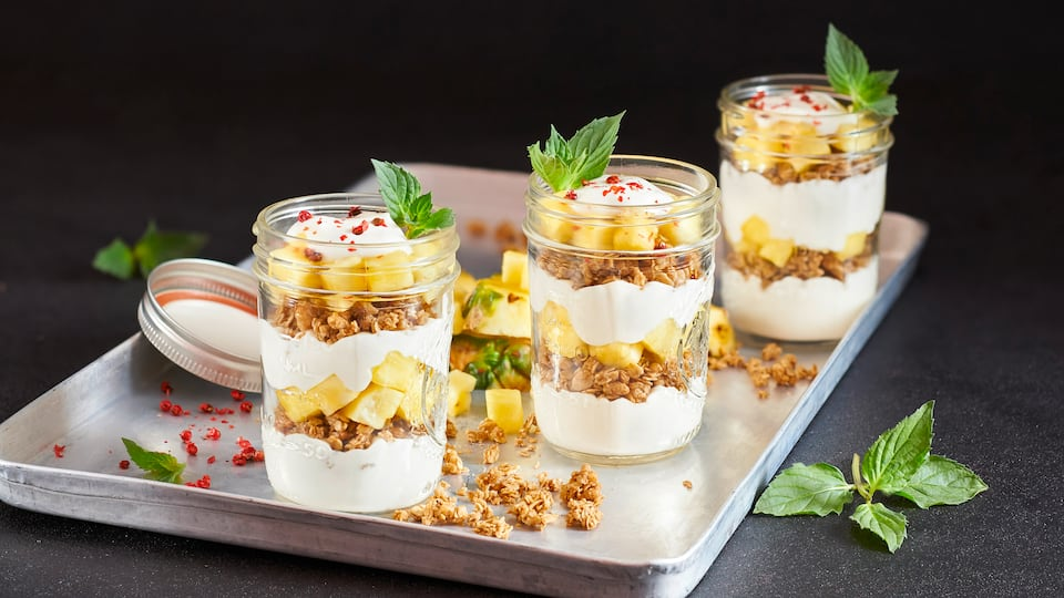 Unser Rezepttipp für ganz viel Power: Probieren Sie unseren Ananas-Protein-Becher mit viel frischer Ananas, Apfelsaft, Skyr und Knuspermüsli!