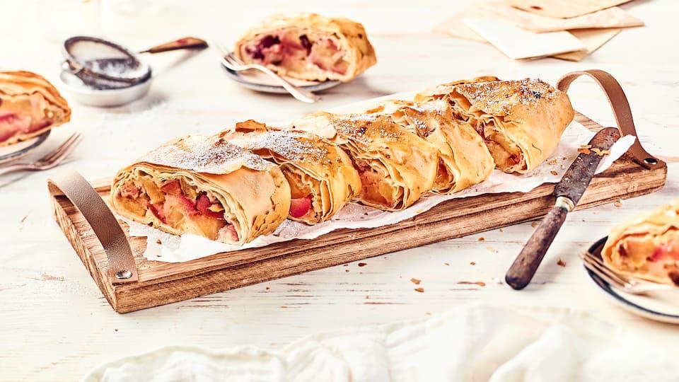 Aus saftigen Äpfeln und knusprigem Strudelteig wird eine köstliche traditionelle Leckerei: Ein Apfelstrudel! Backen Sie süße Füllung in knusprigem Teig!