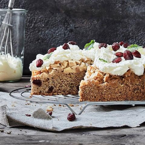 Fruchtiger Kuchen für Ihre Gäste: Probieren Sie unsere Apfeltorte mit Zimt, Mandeln und getrockneten Cranberries! Verziert wird mit Sahne und Beeren.