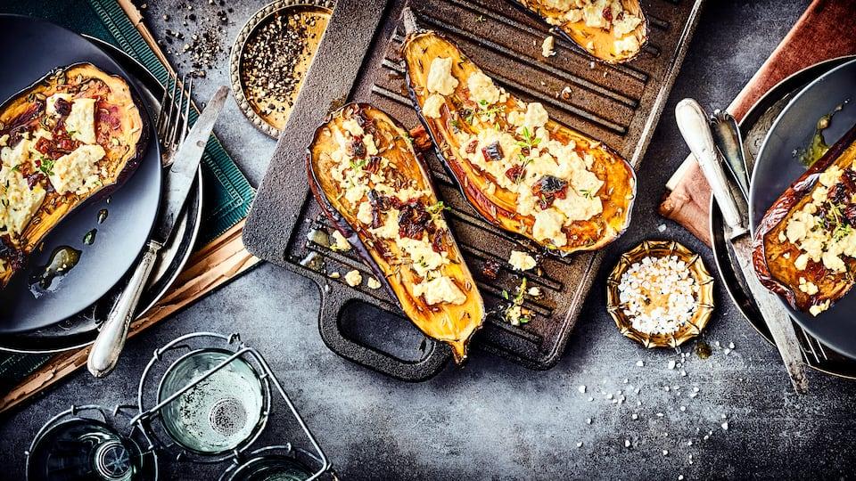 Unser Rezept für gefüllte Aubergine mit Ziegenkäse, Knoblauch-Tomaten-Öl und frischen Kräutern ist vegetarisch und lecker – gleich ausprobieren!