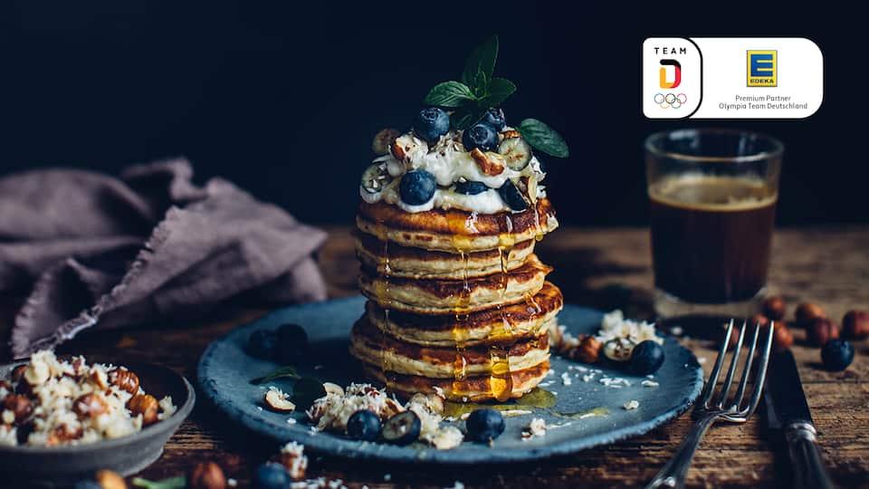 Super viel Power und super lecker! Unsere Bananen-Quark-Pancakes mit Heidelbeer-Topping schmecken nicht zu süß und sind herrlich fluffig.
