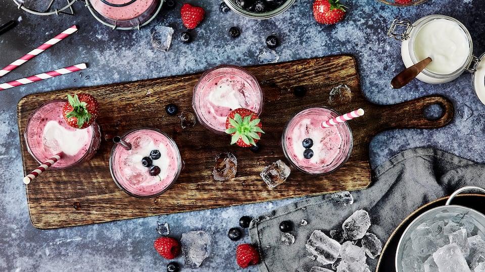 Verwöhnen Sie sich und Ihre Liebsten mit einem erfrischenden Sommerdrink: Probieren Sie unseren Milchshake aus frischen Erdbeeren, Himbeeren, Blaubeeren und griechischem Joghurt!