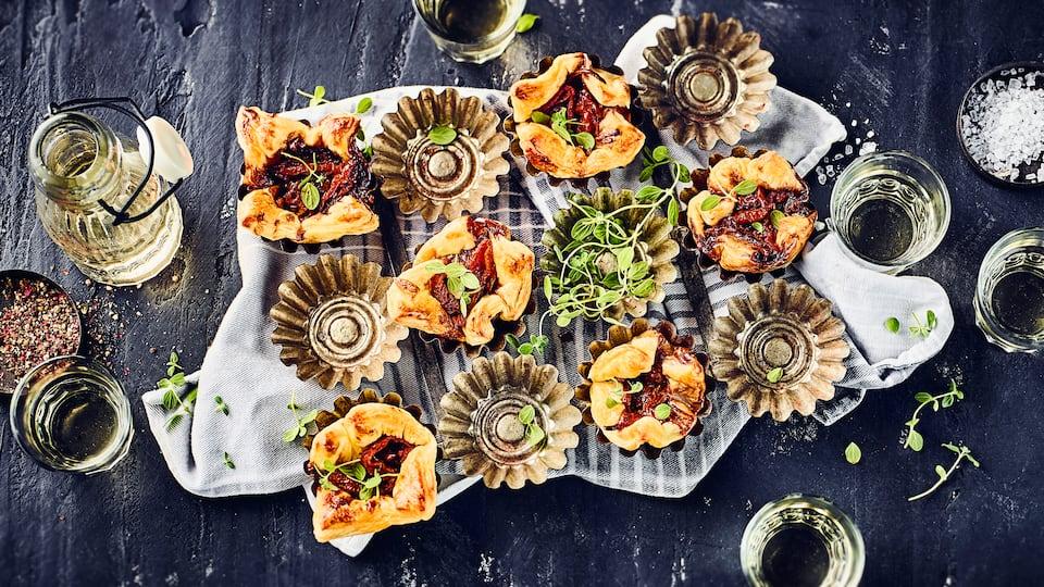 Garantiert der Hingucker auf jeder Party- Probieren Sie unser Rezept für Blätterteigtörtchen mit Tomaten und Zwiebeln in Muffinförmchen gebacken.