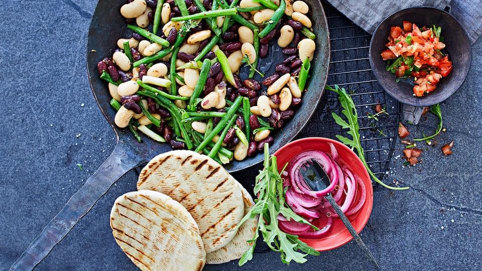 In unserem Rezept für eine Bohnen-Pfanne mit Chili-Tomaten-Salsa kombinieren wir 3erlei Bohnen und servieren dazu eine selbstgemachte feurige Salsa und Pita-Brote.
