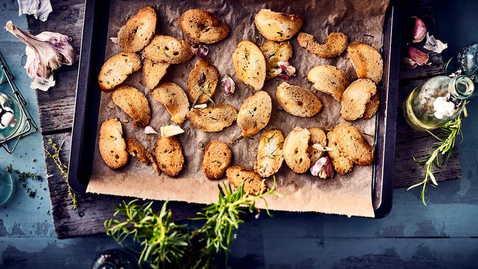 Ideal als kleiner Snack vor der Vorspeise oder als Chips-Ersatz zum Knabbern: Selbstgemachte Brotchips mit frischen Kräutern und Knoblauch.