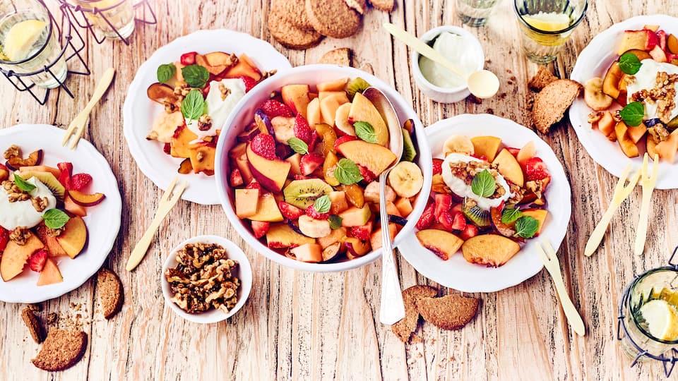 Probieren Sie unseren bunten Obstsalat: Mit exotischen Früchten, karamellisierten Walnüssen und frischer Quarkcreme mit Honig und Ingwer!