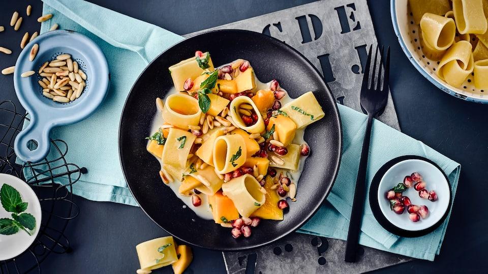 Italienische Calamarata mit Mango, Pinienkernen und Minze. Mit Kokosmilch bekommen die dicken Nudeln einen leicht orientalischen Geschmack und die Soße wird herrlich cremig.
