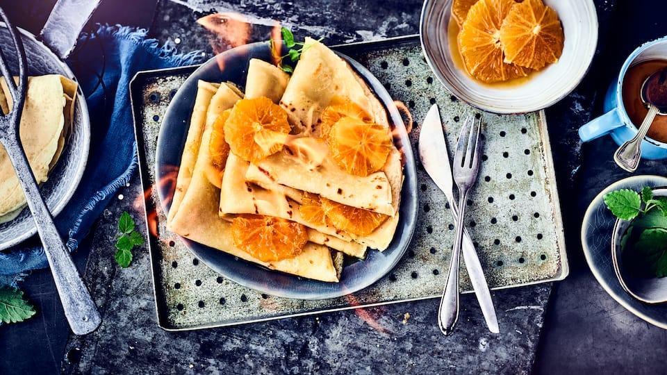 Unser Crêpes-Suzette-Rezept entstammt der gehobenen französischen Küche. Dort werden die hauchdünnen Teigfladen traditionell in Orangenlikör flambiert – es reicht jedoch, die Soße zu karamellisieren.