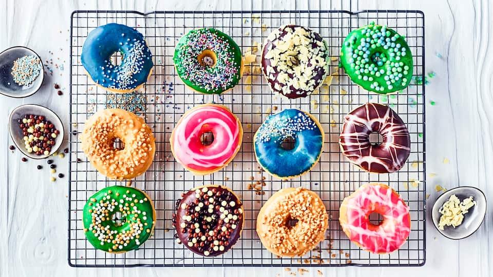 Unser Tipp für die nächste Geburtstags-Party: Probieren Sie dieses Rezept aus und präsentieren Sie selbstgemachte Donuts aus Milch-Hefeteig mit bunter Glasur, hier dürfen Sie sich kreativ austoben!