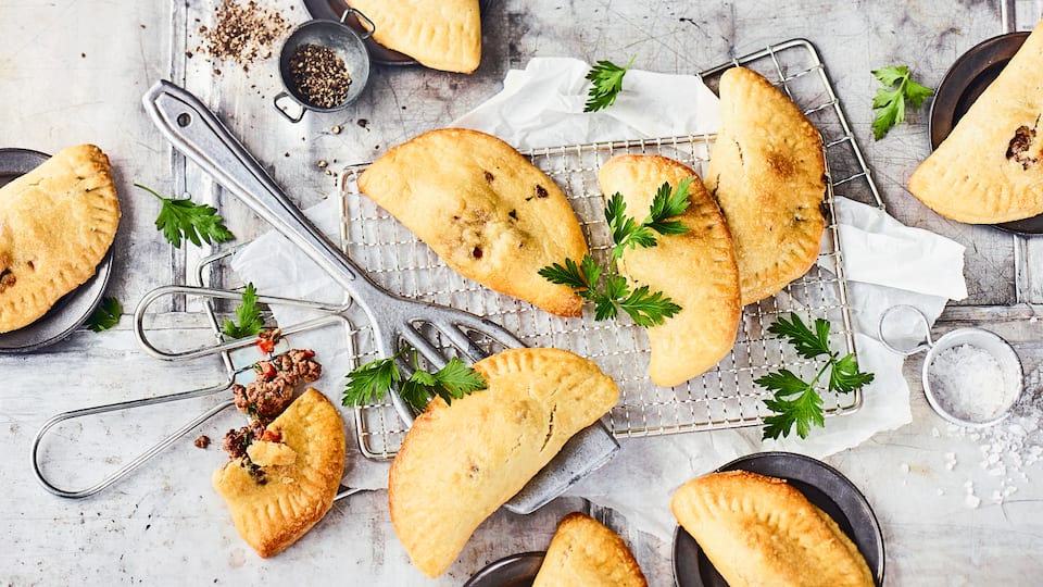 Verpacken Sie aromatisch gewürztes Hackfleisch in Hefeteig und genießen Sie knusprige Empanadas. Wir verraten Ihnen, wie die handliche Köstlichkeit gelingt.