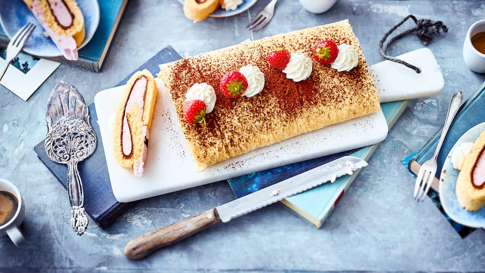 Probieren Sie unser Rezept für eine Erdbeer-Biskuitroulade gefüllt mit einer fruchtigen Quarkcreme mit Sahne und Nuss-Nougat einmal aus – sommerlich frisch!