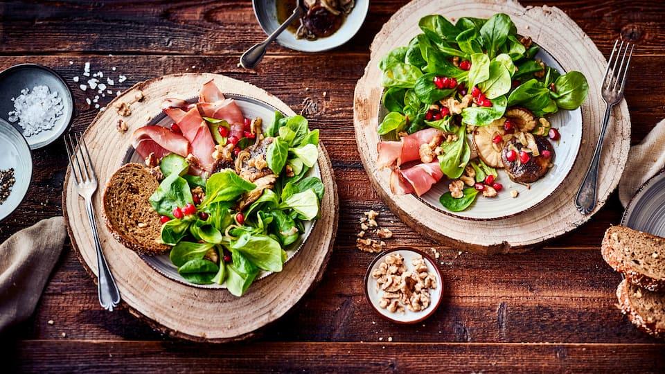 Als leichter Snack oder Vorspeise: Probieren Sie unseren Feldsalat mit Räucherschinken, Walnüssen und Shiitake-Pilzen, garniert mit Granatapfelkernen!