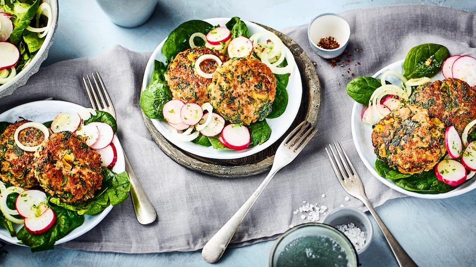 Frikadellen mal anders: Unser Rezept für Frikadellen mit Spinat und Frühlingszwiebeln wird mit einem Salat aus jungen Spinat und Radieschen serviert.