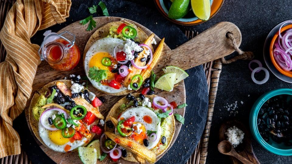 Toast zum Frühstück kennen wir alle, aber probieren Sie doch einmal diese selbstgemachten spanischen Frühstücks-Tostadas aus Maistacos mit Guacamole, Mais, Bohnen, Feta und Spiegelei.
