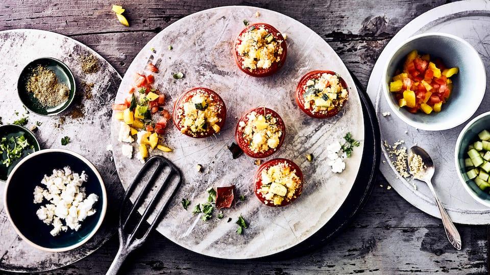 Grillen Sie in nur 30 Minuten vegetarisch gefüllte Tomaten mit Couscous und würzigem Fetakäse – mit Kreuzkümmel und frisch gepresster Zitrone abgeschmeckt.
