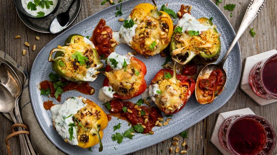 Gefüllte Paprika gibt es in vielen Variationen, aber unsere Variante mit Couscous und einer selbstgemachten Joghurt-Sauce ist mit vielen Gewürzen und Pinienkernen besonders aromatisch.
