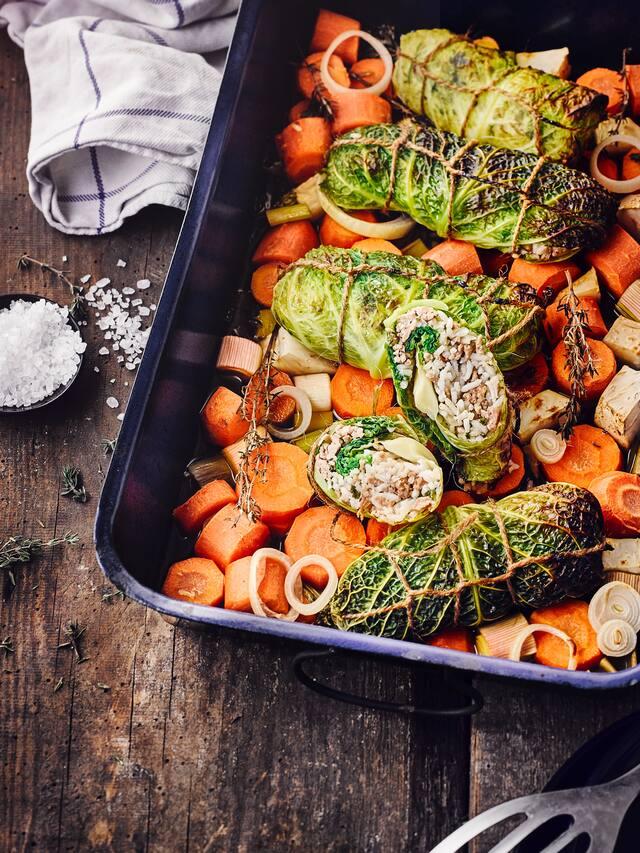 Probieren Sie unser deftiges Wintergericht aus dem Ofen: Mit Reis und Hackfleisch gefüllter Wirsing dazu geschmortes Wurzelgemüse – in 50 Minuten fertig!