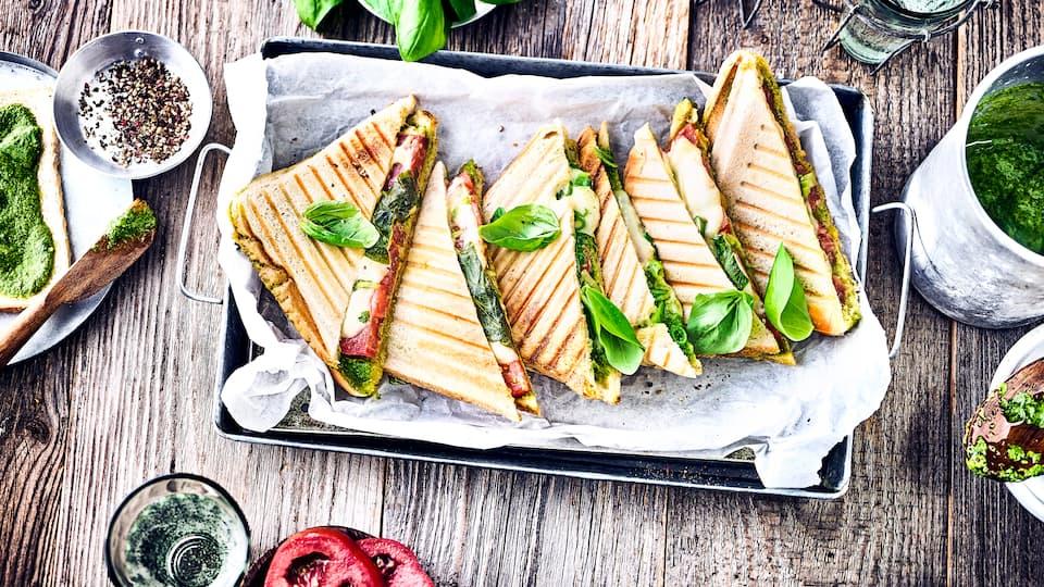 Ruck-Zuck ab in den Sandwichmaker und direkt genießen. Das gegrillte Tomate-Mozzarella-Toast mit selbstgemachtem grünem Pesto ist unsere besonders leckere Variante der leckeren Sandwiches.