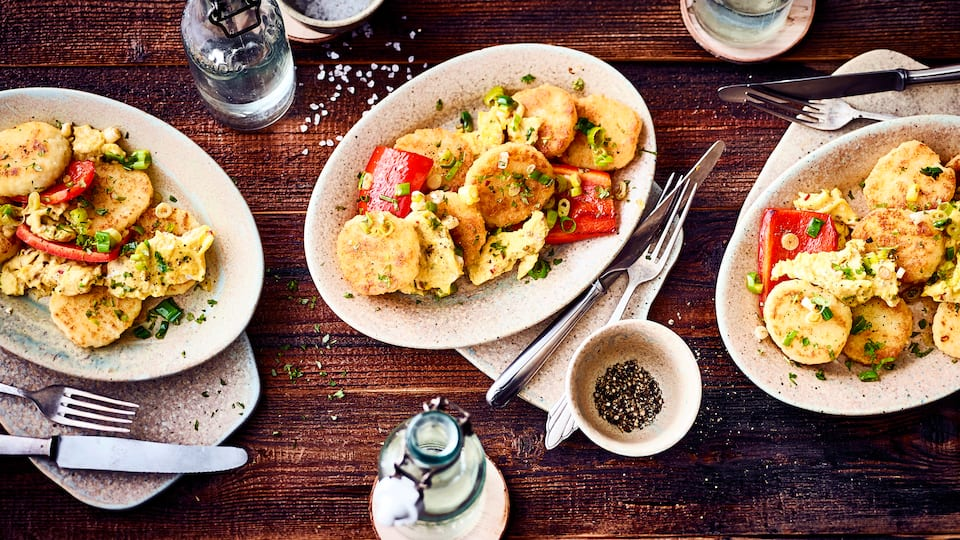 Kartoffelknödel einmal anders zubereitet: In unserem Rezept für geröstete Kartoffelknödel werden die zuvor gekochten Knödel mit Frühlingszwiebeln, Paprika und Eiern in der Pfanne geröstet.