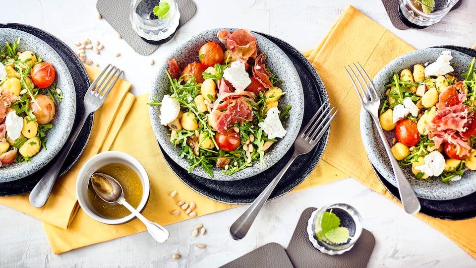 Ein Salat mit leckerem und sättigendem Inhalt: Unser Rezept für einen Gnocchi-Salat mit frischen Gnocchi, Kräuterseitlingen, Serrano-Schinken, Rucola und Ziegenkäse. Dazu passt eine Honig-Vinaigrette.