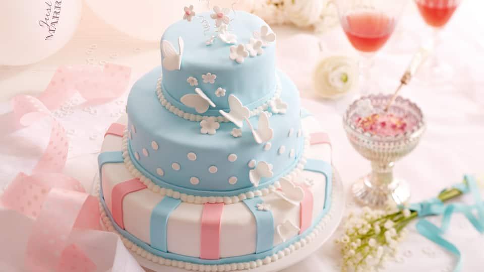 Dreistöckige Hochzeitstorte aus Schokoladenbiskuit, mit Vanillebuttercreme gefüllt und mit Fondant dekoriert.