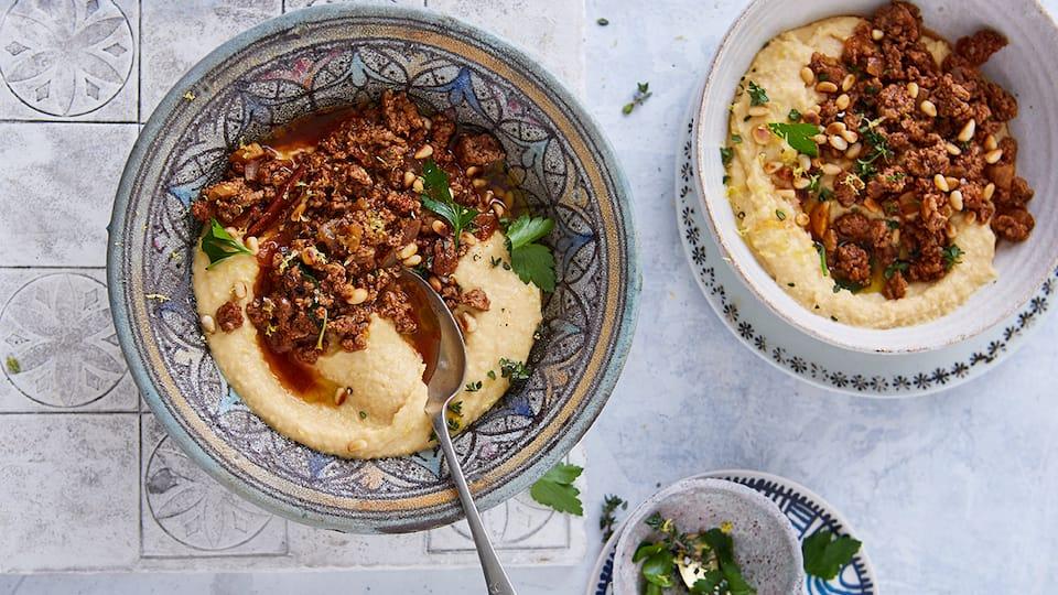 Die orientalische Spezialität Hummus lässt sich einfach Selbermachen: Probieren Sie den cremigen Kichererbsenbrei mit einem Lammsugo und garnieren das Ganze mit Petersilie und Pinienkernen.