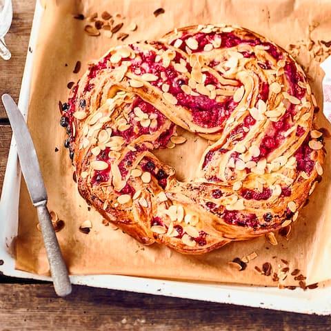 Ein Glanz auf der Kaffetafel: Köstlicher geflochtener Hefekranz mit einer fruchtigen Marzpian-Johannisbeerfüllung.