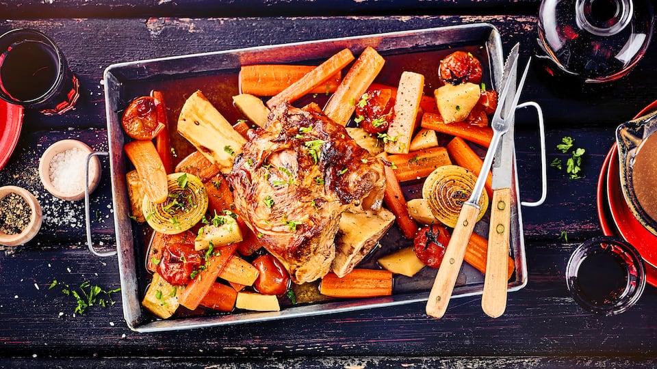 Wir servieren Ihnen heute köstliche Kalbshaxe mit frischem Schmorgemüse – schön saftig und mit Petersilie bestreut ein wahres Gedicht.