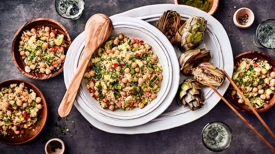 Probieren Sie unser Rezept für einen vegetarischen Kichererbsen-Couscous-Salat einmal aus: Mit Paprika, Gurke und einer Honig-Zitronen-Kümmel-Vinaigrette!