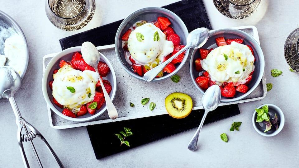 Cremiges Eis aus Kiwis mit marinierten Erdbeeren serviert macht den sommerlichen Genuss herrlich frisch.