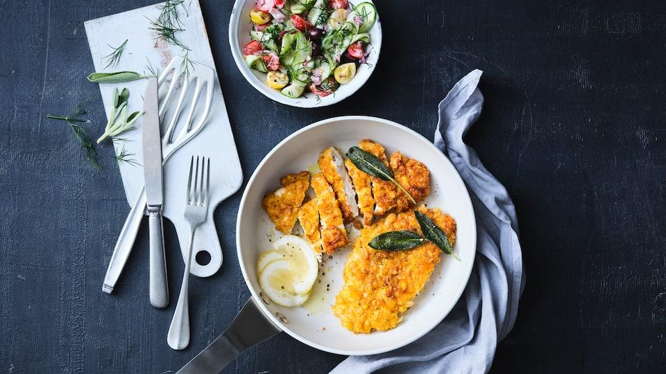 Die Cornflakes sorgen für eine richtig leckere und krosse Panade in unserem schnellen Rezept für Knusper-Schnitzel mit selbstgemachtem Gurkensalat.