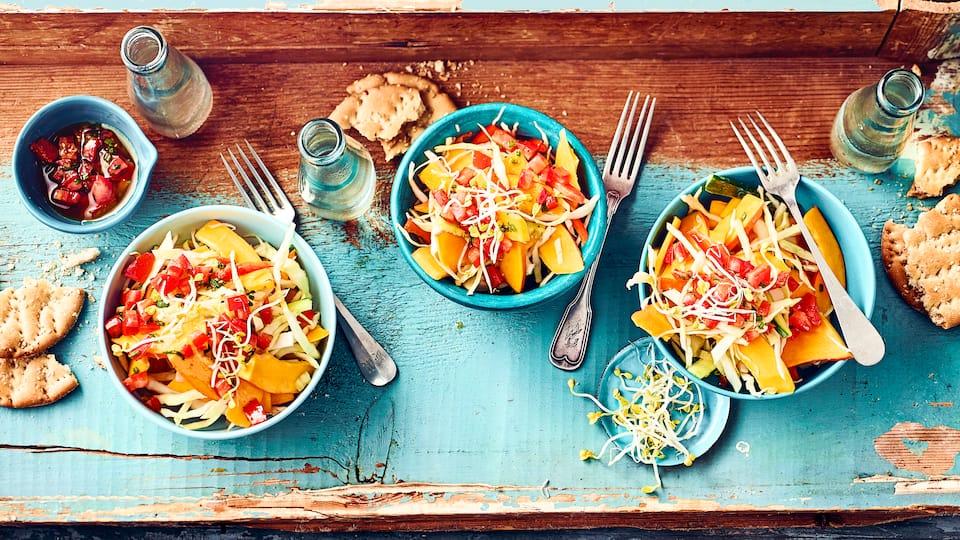 Knackiger Rohkostsalat mit Kürbis, Gurken, Tomaten und Weißkohl, angemacht mit einer selbstgemachten Tomatenvinaigrette und Radieschensprossen.