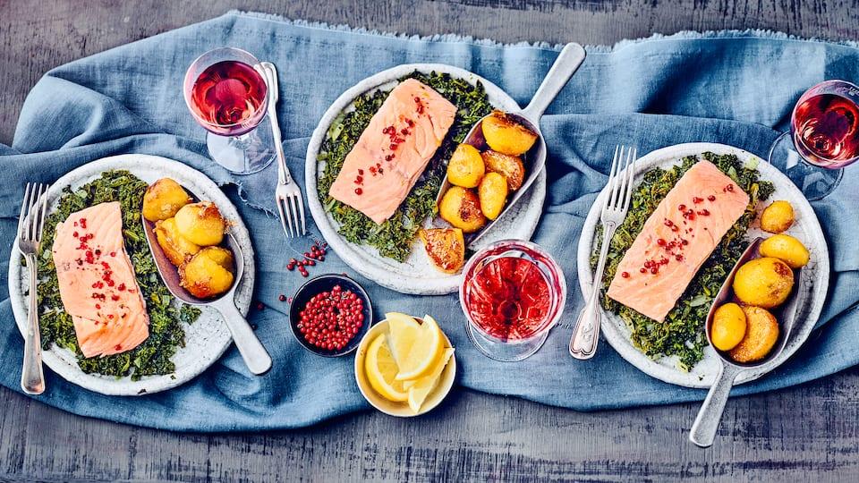 Probieren Sie einmal unsere Variante dieses Traditionsgerichts aus dem Norden Deutschlands: Gedünstete Tranchen von Lachs auf Grünkohl-Gemüse mit karamellisierten Kartoffeln – deftig und lecker!
