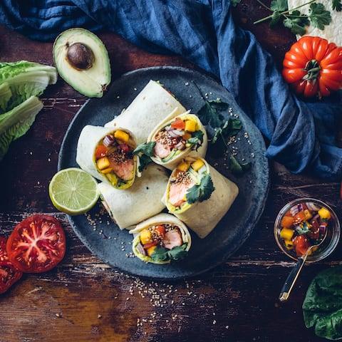 Wir servieren die leckeren Weizentortillas mit Lachs, Avocado und selbstgemachtem Bohnenmus. Eine würzige Mango-Salsa macht unsere selbstgemachten Lachs Wraps perfekt.