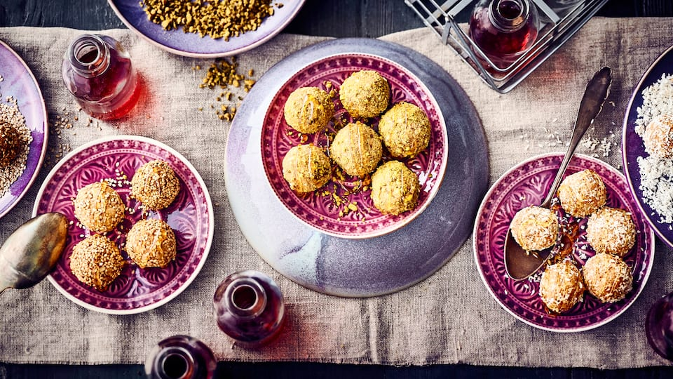 Laddu kommt aus Indien und sind kleine Bällchen, die aus Butter, Kichererbsenmehl, Mandeln und Datteln bestehen und anschließend zum Beispiel in gehackten Pistazien, Kokosraspeln oder Sesamsamen gewälzt werden.