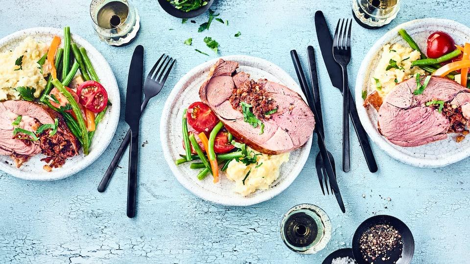 Probieren Sie unsere pikant gefüllte Lammkeule mit einer Gemüsebeilage aus grünen Bohnen, Cocktailtomaten und Paprika – gewürzt wird der Braten mit Harissa.