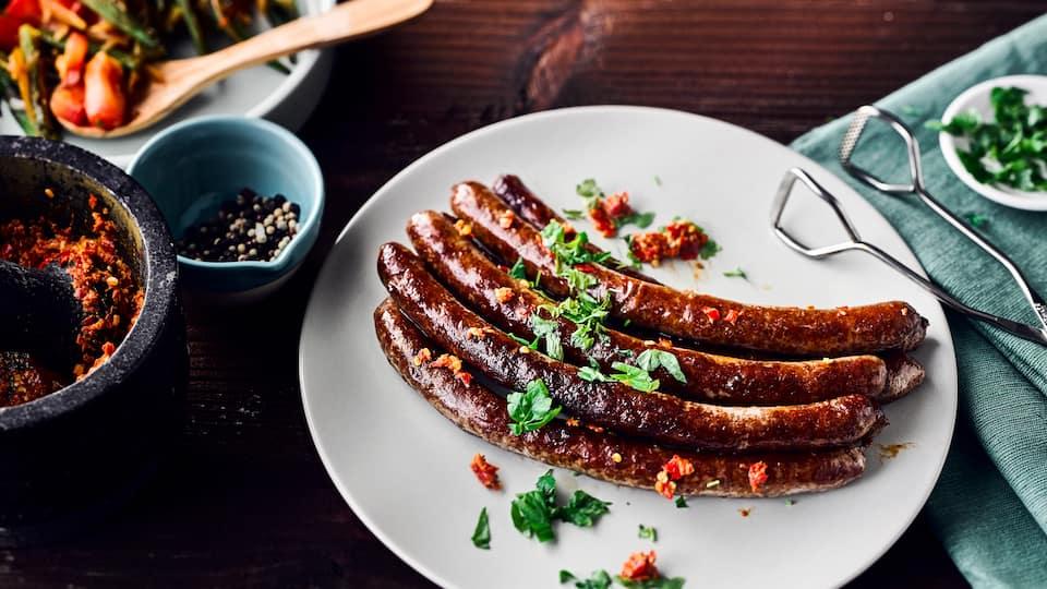 Deftiges für den Grill: Probieren Sie unsere Lammwürstchen mit Harissa, einer scharfen Gewürzpaste aus Chili, Kümmel, Curry und frischen Kräutern!