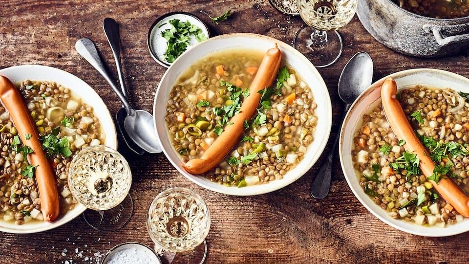 Schnelles Gericht für die kalte Jahreszeit: Probieren Sie unseren klassischen Linseneintopf mit Knollensellerie, Karotten und Tellerlinsen – dazu Würstchen!
