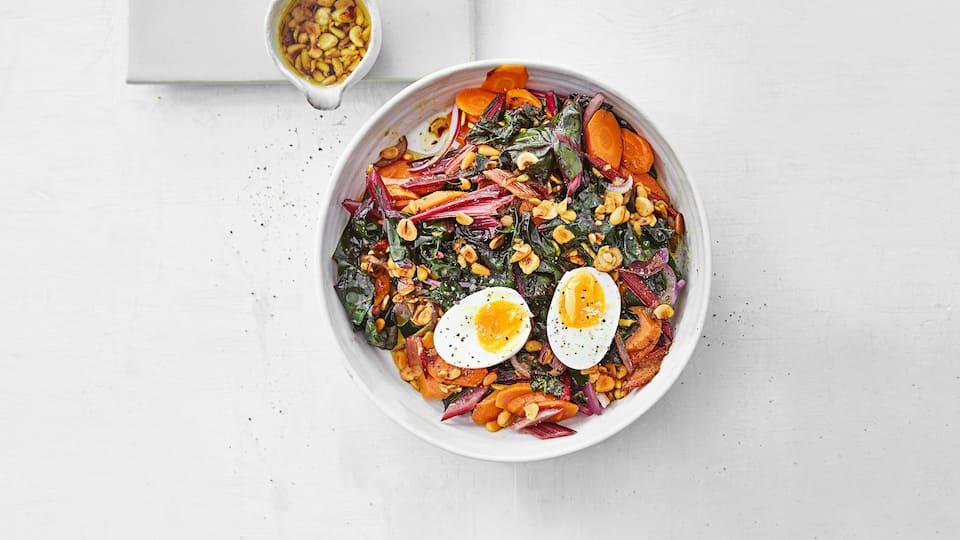 Lecker angebraten ist Mangold ein echter Genuss. Wir kombinieren das saisonale Gemüse mit gerösteten Nüssen und gekochtem Ei.