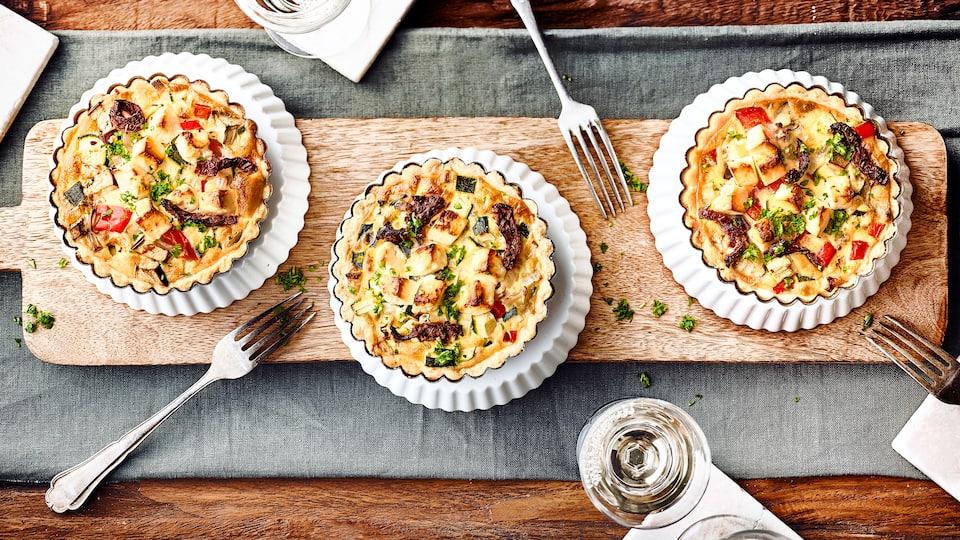 Mediterraner Snack für zuhause: Kleine selbstgemachte Mürbeteig-Törtchen mit allerlei mediterranem Gemüse und Feta.