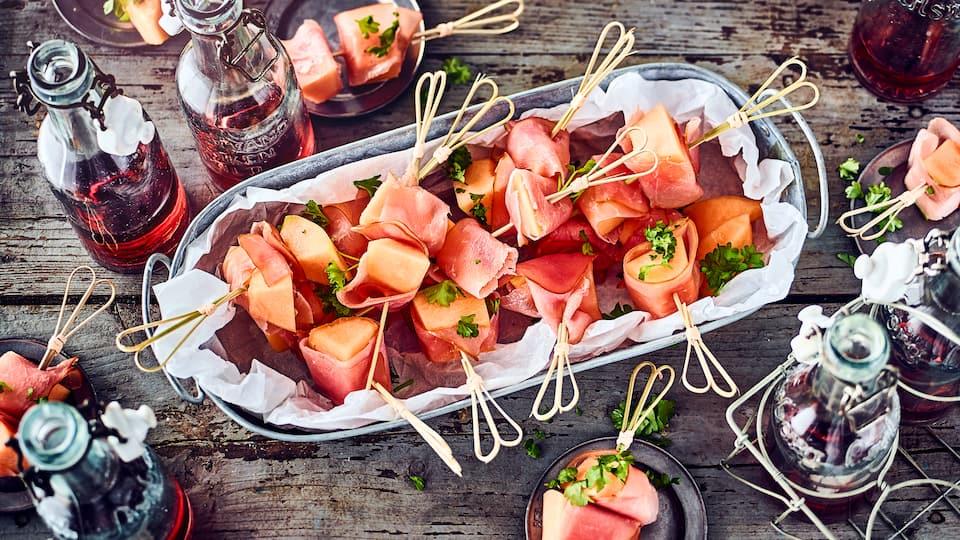 Ganz einfach aber ein leckerer Snack zum Grillabend oder auf dem Buffettisch: Saftige Honigmelone in Stücke geschnitten und mit Schinken umwickelt.