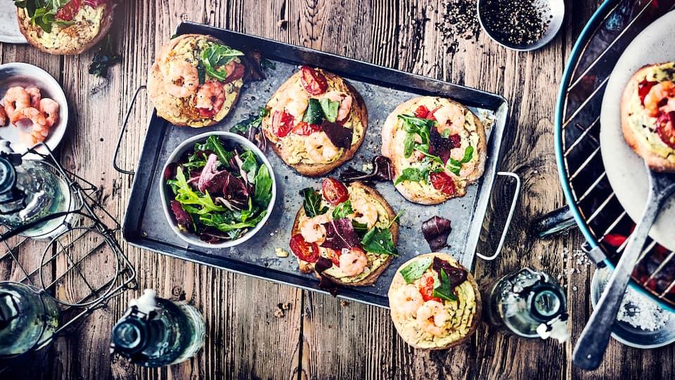 Warum Pizza immer nur aus dem Ofen? Im Sommer schmeißen wir doch viel lieber den Grill an: Genießen Sie unsere kleinen Mini-Salatpizzen mit Garnelen, Tomaten und Rucola!