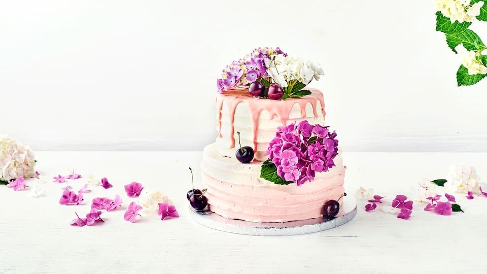 Diese Motivtorte zur Hochzeit bringt sicherlich nicht nur die Braut zum Strahlen! Ein Traum in Rosa mit Blumenblüten und Kirschen verziert.