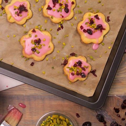 Backen Sie unsere fruchtigen Kekse aus Mürbeteig! Getrocknete Cranberrys, Cranberrysaft und gehackte Pistazien geben den Plätzchen ihren süß-säuerlichen Geschmack –perfekt für Geburtstage und Partys.