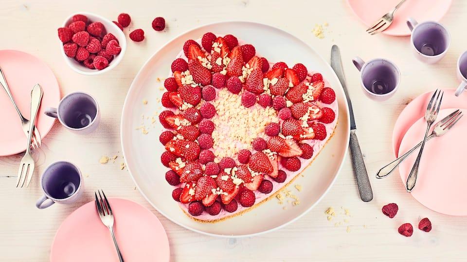 Luftiger Biskuit, gefüllt mit einer köstlichen Erdbeer-Vanillecreme mit Erdbeerlikör und anschließend mit Erdbeeren, Himbeeren und weißer Schokolade dekoriert.