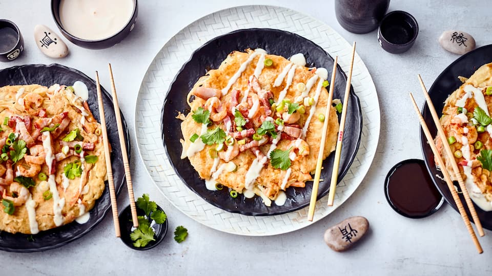 Okonomiyaki kommen aus Japan und sind eine Art dünner Pfannkuchen, der mit einer typischen Okonomiyaki-Sauce gewürzt und mit Speck, Zwiebeln und Garnelen belegt wird.