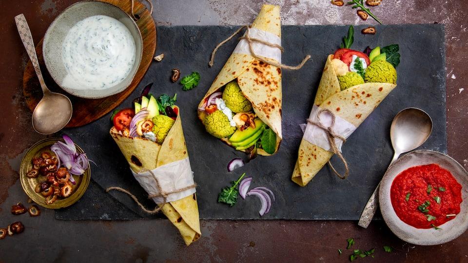 Einen orientalischen Touch bekommt unser Rezept für Falafel Wraps durch die Füllung mit Ajvar und Hummus und den leckeren Koriander-Minz-Joghurt.