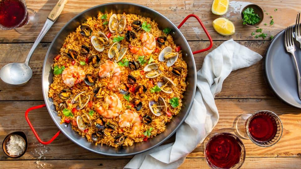 Unsere klassische Paella mit Meeresfrüchten, frischem Gemüse und Safran ist ein intensiv aromatisches Reisgericht mit Tradition und eine herzhafte spanische Spezialität, die zu jeder Gelegenheit kulinarisch überzeugt. Probieren Sie selbst!