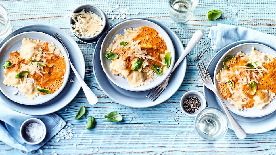 Selbstgemachte Ravioli gefüllt mit einer Mischung aus Parmesan, Oliven und Tomaten, serviert auf einem feinen Paprikaschaum mit Sahne.